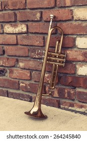 Old worn trumpet stands alone against a brick wall outside a jazz club