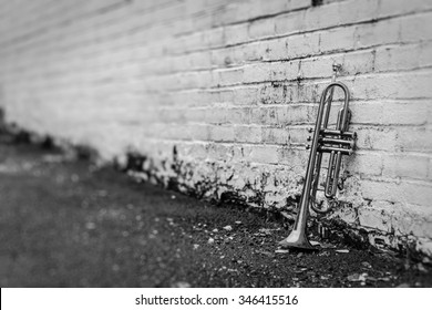 Old worn trumpet stands alone against a grungy pealing white brick wall outside a jazz club