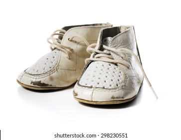Old worn vintage leather white baby shoes isolated on white with natural shadows.