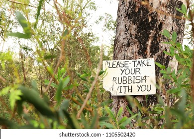 old worn warning sign on a tree telling campers hikers people to remove all rubbish trash litter. illegal dumping concept environmentally responsible. bush rural forest setting. leave nothing behind