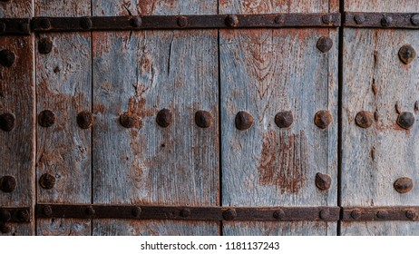 Old, worn, wooden door with rusted metal slats and bolts background texture