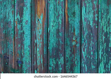 Old worn wooden planks with worn, cracked paint of a turquoise-green color with rust. Beautiful wooden aged background.