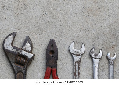 Old wrench tool with rust placed on the concrete floor background and have copy space for design in your labor day concept.