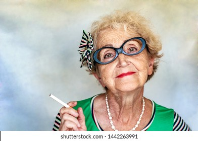 Old wrinkled fashionable woman in glasses with a cigarette in hand. Women's health, bad habits, addiction