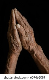 Old wrinkled hands praying isolated on black