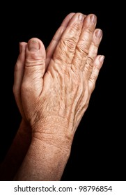 Old wrinkled hands praying isolated on a black background