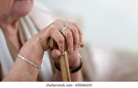 Old wrinkled woman hands holding walking stick