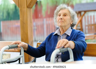 Old wrinkled women hand hold walker