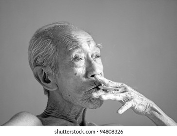 An old wrinkly emaciated Chinese man smoking a cigarette in monochrome.