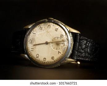 Old wristwatch on black background