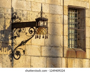 Old wrought iron lamp and window with security bars on the stark wall of the Convent of San Paio de Antealtares on the Quintana Square (Praza) - Santiago de Compostela, Galicia, Spain