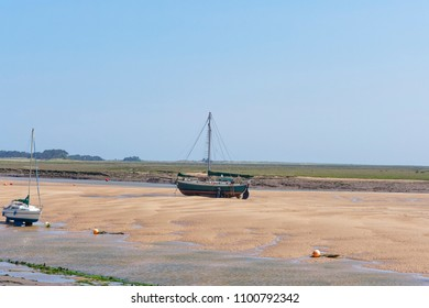 An old yacht sits on a sandbank at low tide in an estuary. Salt marshes stretch out in to the distance