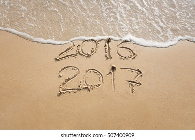 Old year 2016 and new year 2017 written on sand near the sea, wave washes away 2016