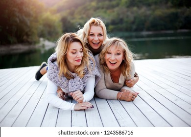 old years mother with her two daughters relaxing on the lake, laughing, speacking and enjoying the view of lake and mountains