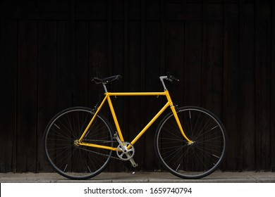 Old yellow bike against dark wood wall. Yellow singlespeed bike. Yellow single speed Favorite bike.