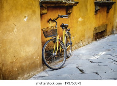 An old yellow bike leaning up against a yellow wall somewhere in Italy
