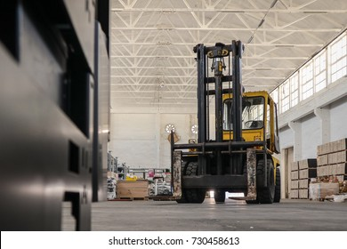An old yellow and black forklift is waiting to pick a next load in white warehouse.
