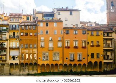 Old yellow buildings hang over the river