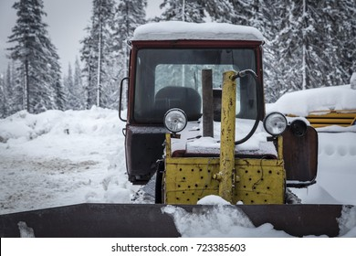 An old yellow bulldozer covered with snow stands in the mountains against the background of snow-covered fir trees. Ukraine. Carpathians