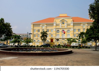 The old yellow colonial Ministry of Post and Telecommunications building across the road from a circular fountain in Phnom Penh, Cambodia on Daun Penh Avenue.
