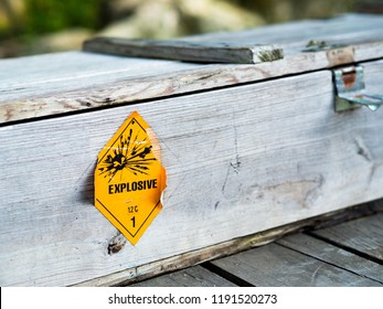 Old yellow explosive hazardous pictograph sign on wooden grungy weapon military chest box. Danger warning sign for Propellant explosive substance with a blast hazardous materials class 1.2