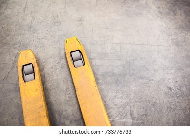 Old yellow fork lift paddles in the warehouse close up.