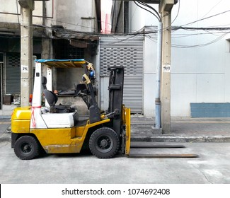 Old yellow forklift truck parked on the roadside in the city.