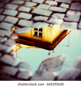 Old yellow house in reflection of puddle on pavement. European vintage city view. Cozy street