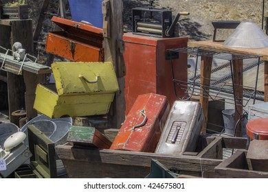 Old yellow, metal toolbox sitting on a pile of other old toolboxes and other metal junk.