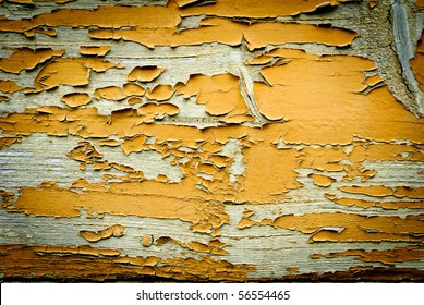 Old yellow paint coming off wooden boards
