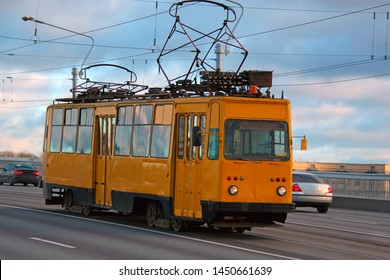 old yellow tram with two pantographs rides over the bridge