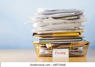 An old yellow wireframe filing tray, piled high with documents and folders, on a light wood veneer desk against light blue background.