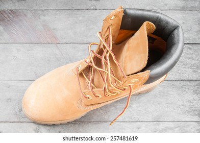 old yellow working boots on wood background