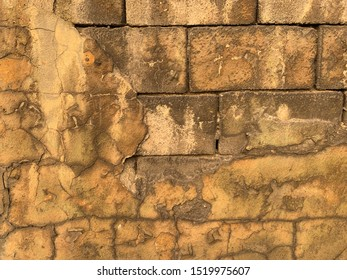 Old yellowed brick wall with fallen stucco. The brick wall is visible from under the cracked yellow plaster. Stucco and brick wall texture. Piece of brick wall under plaster