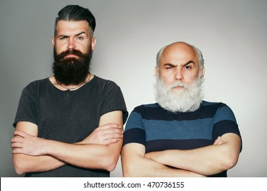 Old and young bearded men with long beard white and brown and raised eyebrow in studio on grey background
