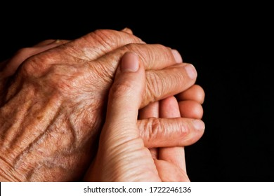 Old and young hands close-up. Aged good grandmother's hands in the hands of a young girl. Youth passes quickly. Youth and old age. Young and old hands top view. Appreciate youth she is passing soon
