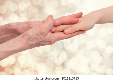 Old and young holding hands of each other, on a light blurred background.