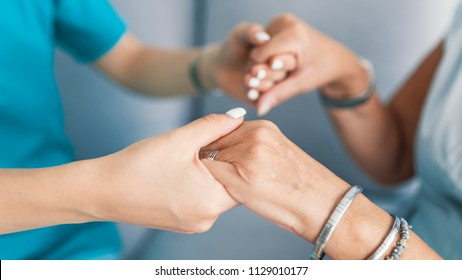 Old and young holding hands on light background, closeup. Helping hands, care for the elderly concept. Care is at home of elderly. Woman with caregiver at home