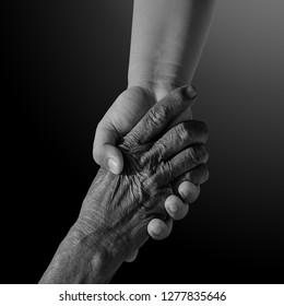 Old and young person holding hands. Elderly care and respect, .black and white photography. space for text.family, generation, support and people concept -senior man and child holding hand