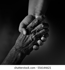 Old and young person holding hands. Elderly care and respect,