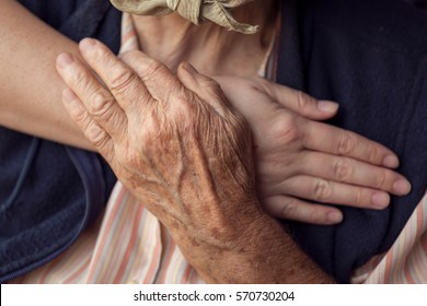 Old and young person holding hands. Elderly care and respect, selective focus