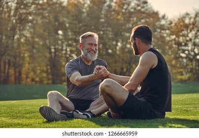 The old and young sportsmen greeting on the grass