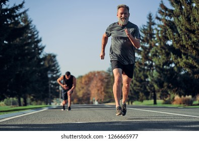 The old and young sportsmen jogging on the road