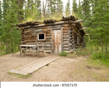 "Old Yukon log cabin hidden in the boreal forest (taiga) of Yukon Territory, Canada with chair and table on outside ""terrace""."