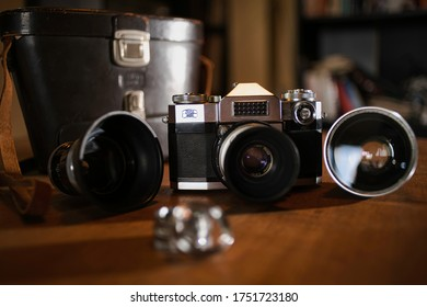 The old Zeiss Ikon camera photographed up close on a wooden desk with lens beside it