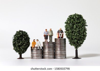 Old-age miniature people on a pile of coins between miniature trees.