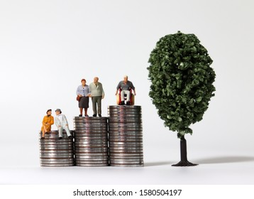 Old-age miniature people on a pile of coins with miniature trees.