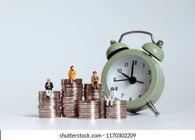 Oldage miniatures sitting on a pile of coins with alarm clock.