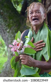 Olde aged Pacific Islander man (age 75)  explains about exotic  flower on eco tourism tour in Rarotonga Cook Islands. Real people. Copy space.