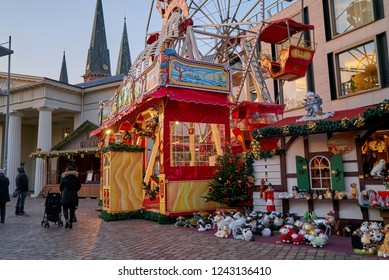 "Oldenburg, Germany - November 28, 2018: part of the ferris wheel and a hut at the famous Christmas market ""Lamberti Markt"" in front of the church St. Lamberti and the palace guard building"